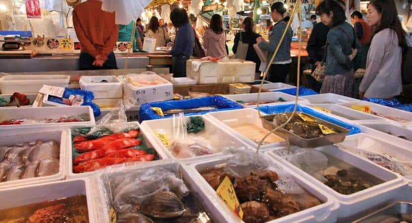 A display of various types of seafood in Styrofoam containers at a Japanese market.