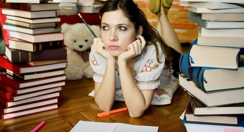 A young woman lying down on the ground holding a black pencil in her right hand. Her elbows are on the ground, her hands cupping her face. Stacks of books surround her, and a light brown teddy bear is also seen in the background.