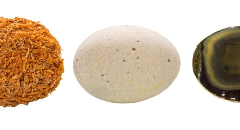 3 pieces of Pitan, or Chinese Century Eggs. On is unshelled, one is in its shell, and the other is covered in some kind of brown material.