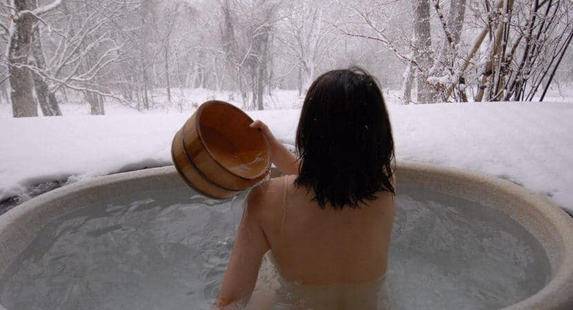 A woman with black hair is soaking in a Japanese Rotenburo (open air bath) while looking at the snow and trees all around her.