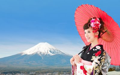 Mt. Fuji is in the background. A young Asian woman dressed in a multi-colored kimono holding a pink Japanese style umbrella is looking off to the left side of the picture.
