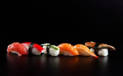 6 pieces of nigiri Sushi displayed in a line. (Fish, imitation crab, cucumber, salmon, shrimp, and unagi sushi).