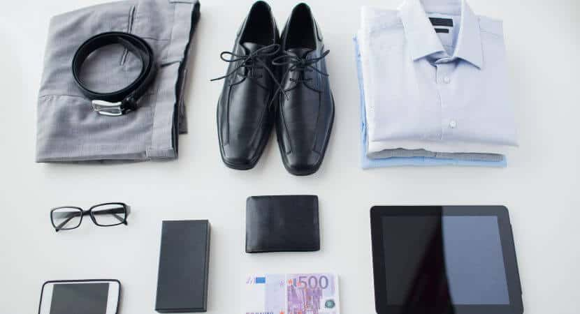 A folded pair of grey pants with a black belt on top, a pair of black dress shoes, three folded button up shirts, a pair of glasses, a smartphone, a wallet, a longer pocket wallet, a electronic tablet and cash on a white surface.