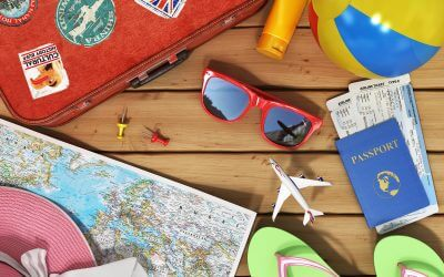 A red suit case with travel stickers on it. A pair of sunglasses, a hat, a map, green slippers, a beach ball, a small model airplane, a yellow bottle, thumb tacks and a blue passport book with two tickets inside are also shown.