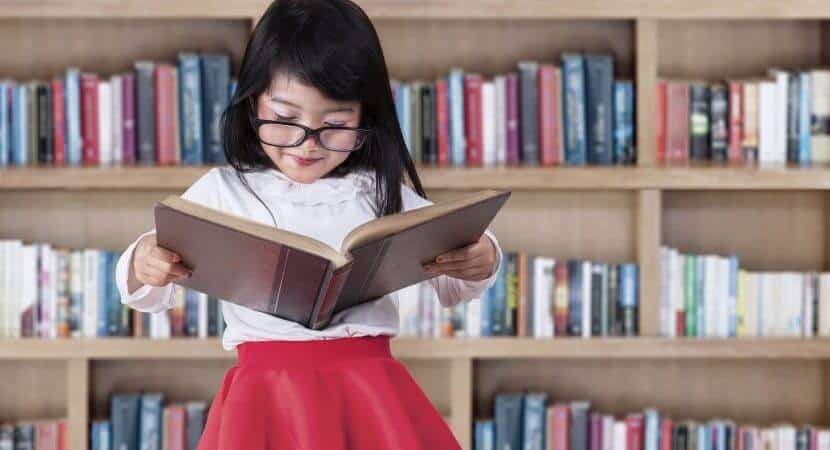 A young Asian girl is standing while holding a book that she is reading. A bookshelf full of books is behind her.