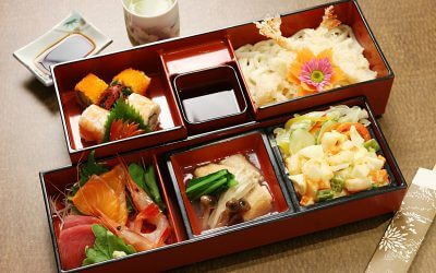 2 Japanese style of teishoku (set meal) boxes. In each section of the box (6 in total, 3 in each box) there is a different food item or sauce in it). A saucer of soy sauce and a cup of green tea is next to the boxes, and a pair of disposable chopsticks at the opposite corner.