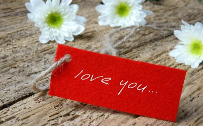 "A red tag with a string attached that reads, ""love you..."" in white lettering. It is resting on a wooden surface, with white/yellow flowers in the background."