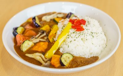 A plate of curry and rice, with vegetables (yellow bell pepper, eggplant, mushrooms, etc.).