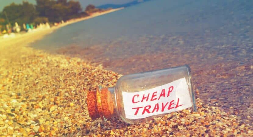 """A Message in a Bottle on the beach that has the words, """"Cheap Travel"""" written on it."""