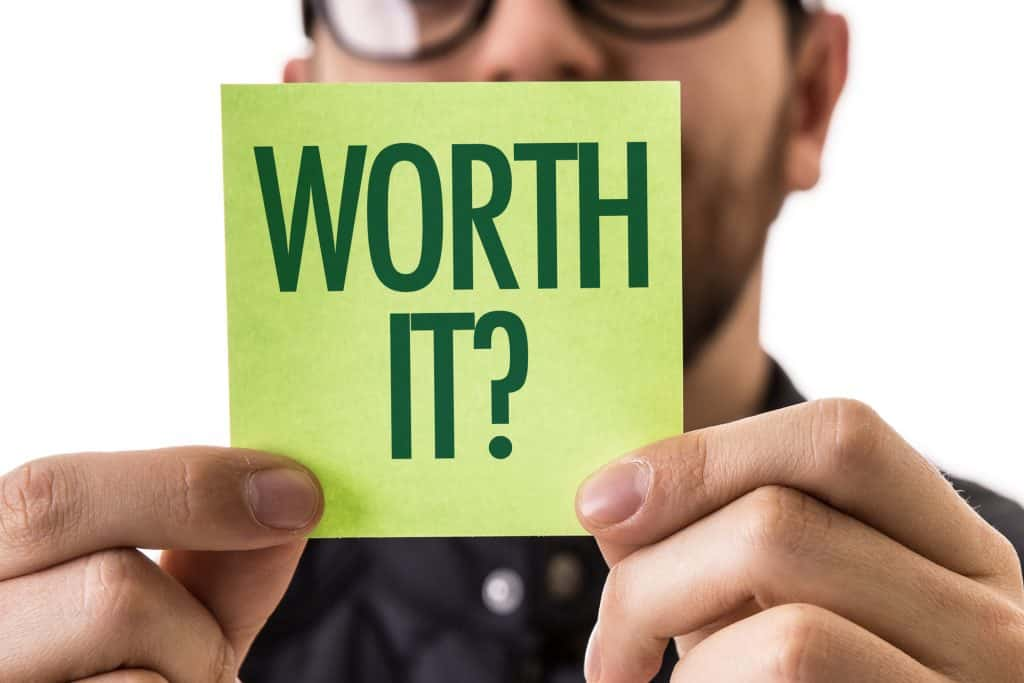 "Man holding up a green Post It sized paper that says ""WORTH IT?"""