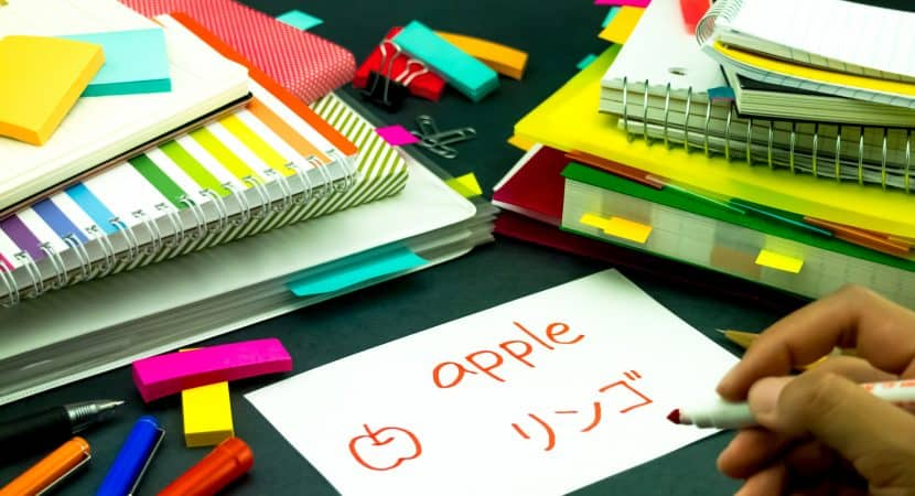 "Two stacks of notebooks and folders with a bunch of color mini Post-It notes scattered all around. The the center is a white flashcard with the word, ""apple"" written on it in red. There is also a hand-drawn picture of an apple and Japanese characters on the same flashcard, also in red. Someone's hand can be seen holding a red pen."