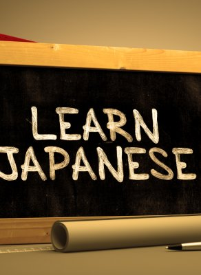 "A small rectangular chalkboard with the words, ""LEARN JAPAENSE"" written on it in white chalk. Behind the chalkboard are a stack of books. In front of it is an alarm clock, paper rolled into a tube. a pen, and a ruler. On the right side is a pencil holder with pencils in it."