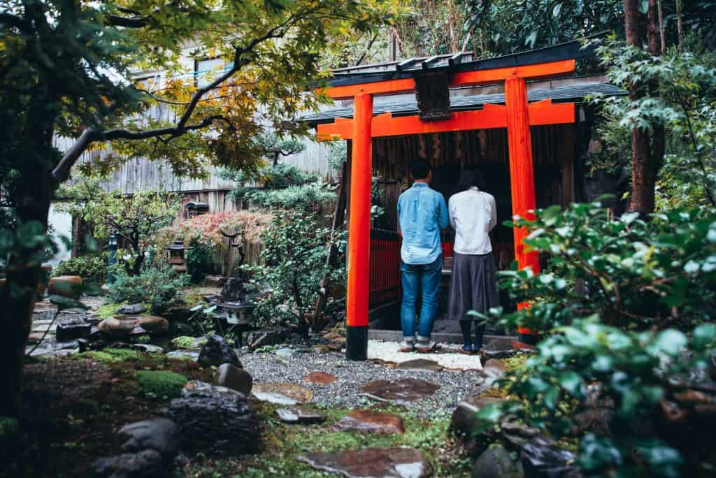 Praying at a small ShintoTorii Gate