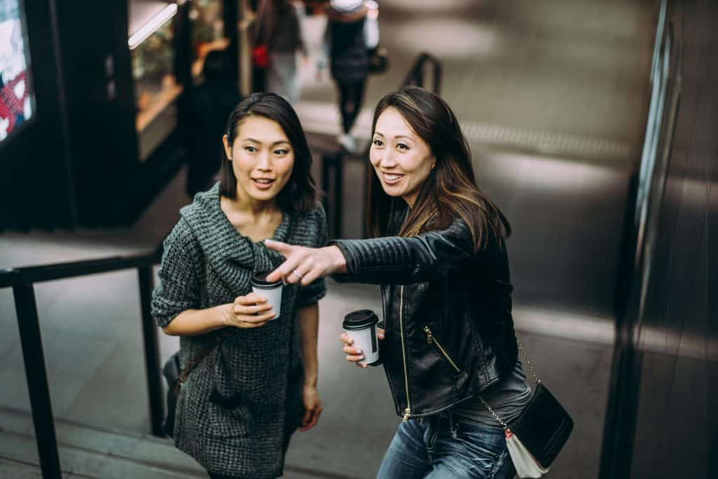 One Japanese woman giving another woman directions by pointing