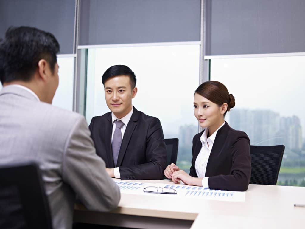 Young Asian man and woman talking to another man, who seems like their superior in an office.