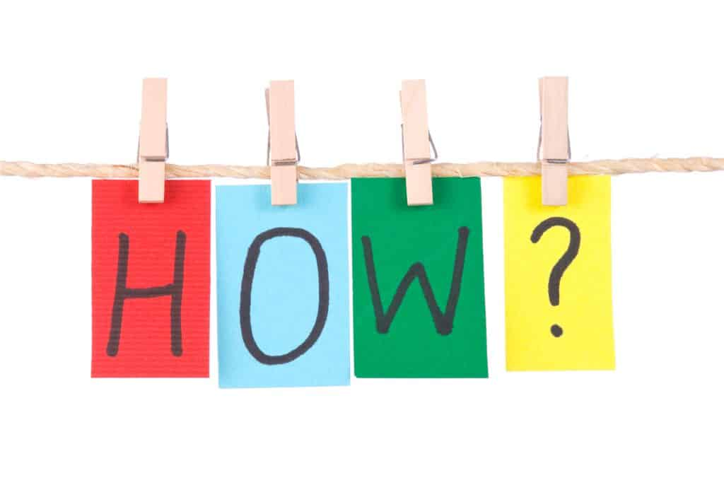 """The word """"HOW?"""" spelled out with each letter on one piece of colored paper (red, light blue, green, and yellow, respectively) hanging from the clothesline with clothes pins."""