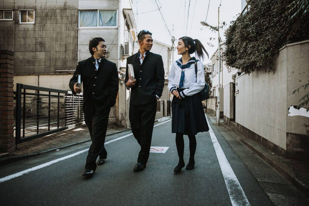 Two young boys and a young girl dressed in a Japanese school uniform. They are talking while walking down a residential road