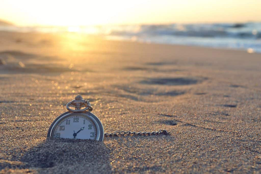 An older, metal stopwatch halfway embedded in the sand on a beach with the sun setting in the backgroun