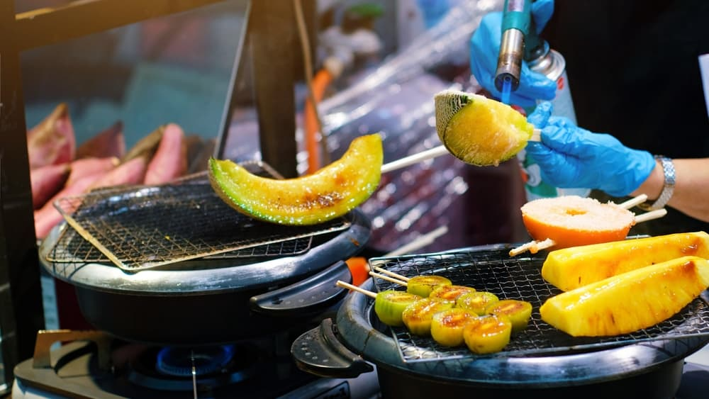 Food vendor at the outdoor Kuromon Market in Osaka. They are grilling slices of melon with a blowtorch.