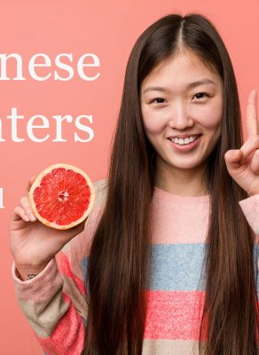 A cute, young, Asian girl holding a half an orange in her right hand and showing the number one with her pointer finger on her left hand