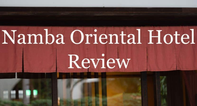 "Red cloth hanging from a Japanese style door-front that says the title of this article, ""Namba Oriental Hotel Review."""