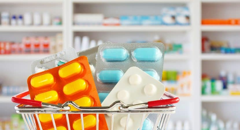 Medicine pill tablets in their pill packs, which is in a mini shopping cart with a blurred view of a pharmacy drugstore's shelves in the background.