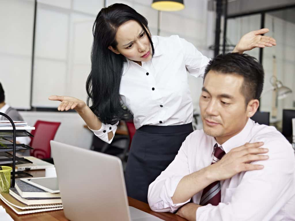 Asian male sitting at his desk working on his laptop while a young asian woman is shrugging her shoulders looking angrily at him