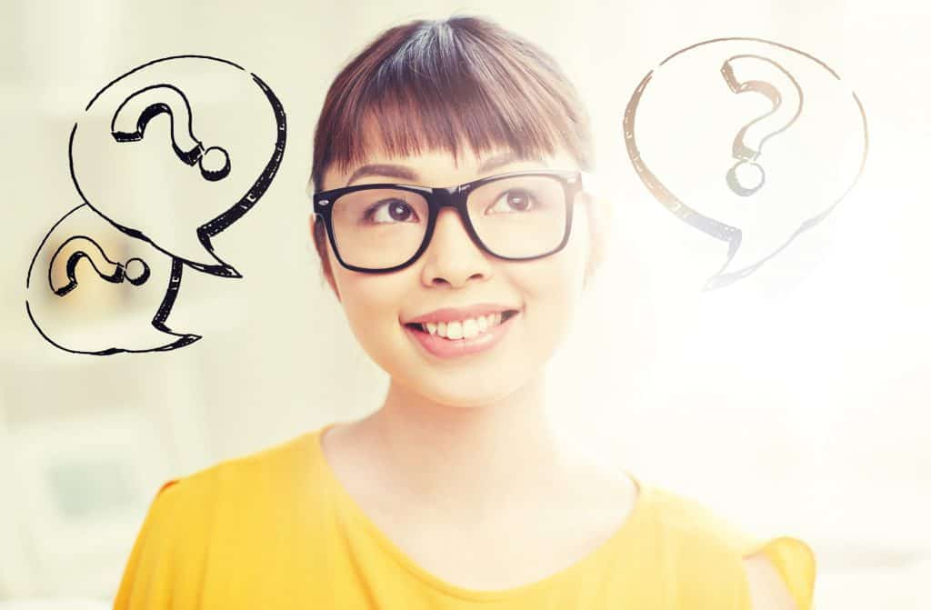 Young Asian woman with glasses wearing a yellow top smiling but with a slight confused look on her face. Question marks in speech bubbles are surrounding her head
