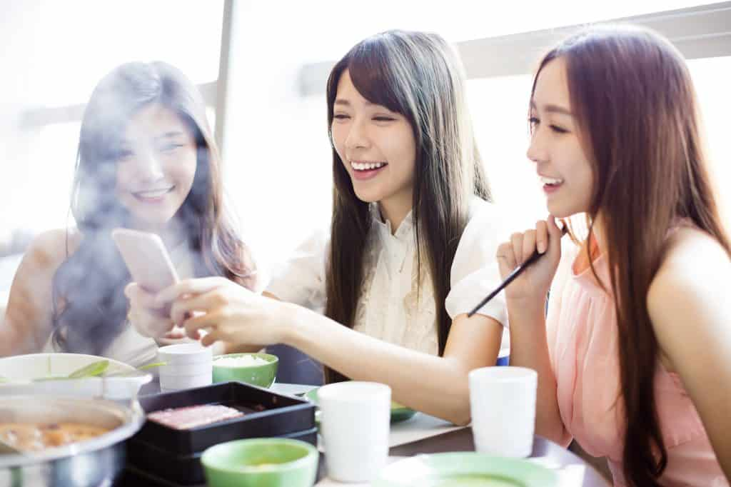Three young Asian women sitting at a table eating hot pot. The woman in the middle is holding a smartphone, which all three of them are looking at and smiling.