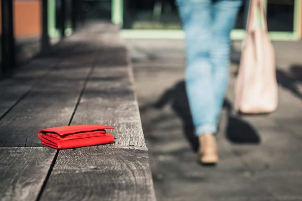 A woman wearing jeans hold a beige bang is seen in the background, walking away from a red wallet left on a bench.