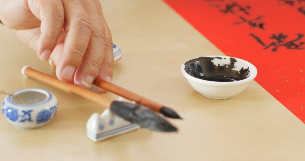 A picture of someone's hand about to take one of two calligraphy brushes resting on a small stand on the table. In the backgroud there is a small white dish filled with black ink and a red paper with Chinese characters written on it.