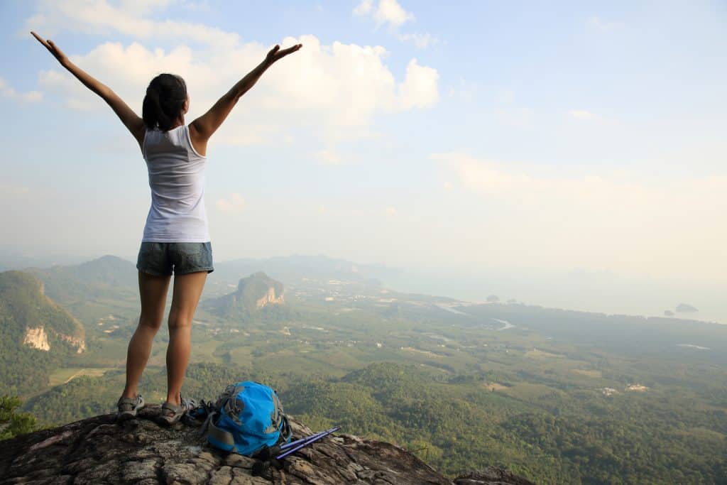 A girl on the edge of a cliff overlooking the green nature and a body of water below. The girl is wearing a white tank top and jean shorts, and has both of her hands raise up above her head.