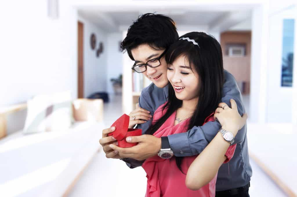 A young Asian couple. The man is embracing the woman from behind, holding and showing her a ring in a red box. The woman is holding the man on his shoulder, while smiling at the ring. The woman is wearing a pink outfit and the man is wearing a long sleeve grey shirt.