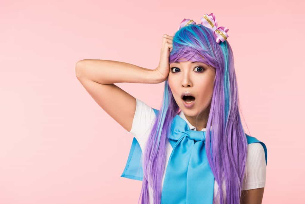 A young Asian girl with long purple and blue hair, dressed in a white and blue outfit. The blue part of her outfit has a bow tie by her neck. She has her right hand on the side of her right temple, with her mouth open to express shock or surprise.