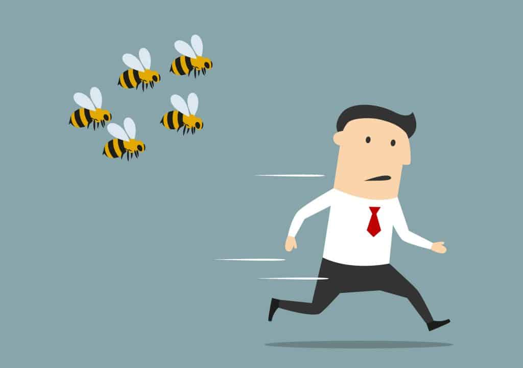 A cartoon illustration of a businessman was attacked by swarm of angry bees (to the left of the image). The man is wearing a long sleeve white shirt, black pant trousers, and a red tie.