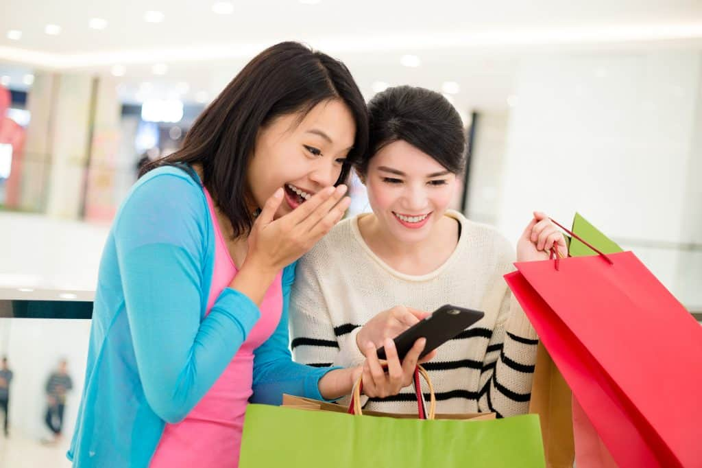 Two young Asian woman looking at a cellphone while holding a bunch of green and pink shopping bags. They looked suprised.