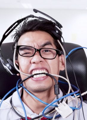 A young Asian man wearing glasses sitting down with headphones on his head. He also is tangled in a bunch of wires, and is biting down of them to express frustration.