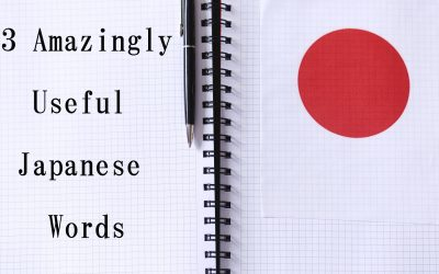 "An open note book with a the text ""13 Amazingly Useful Japanese Words"" written on the left page, with a paper with a red circle on the right page. A pen is resting on top of the left page."