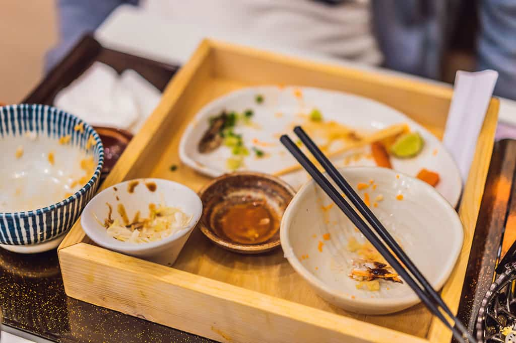 A wooden Japanese lunch box with 4 smaller dishes inside of it with a pair of black chopsticks resting on top of a dish. There is a blue and white bowl on the side of the lunch box. All of the dishes have the remains of food, most of which has been eaten.