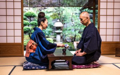 A traditional Japanese room with tatami style mats, with the door open that looks out into a green Japanese garden. In the center is an elderly Asian man and woman seated on a cushion on their knees, with a black table between them. The woman is pouring the man a cup of tea.