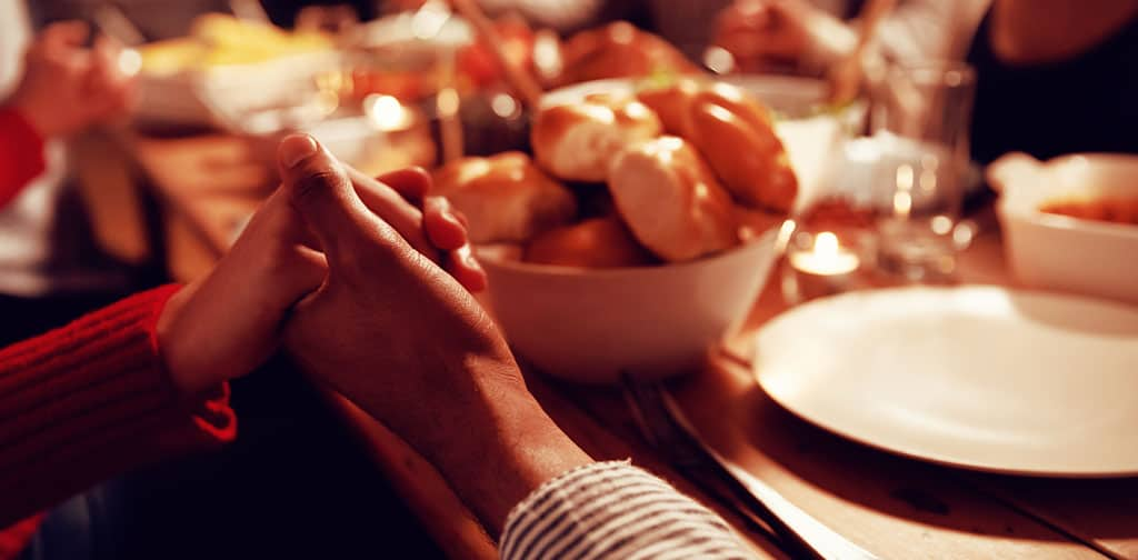 A close-up of a man and woman holding hands while seated at a dinner table to say grace. There is a basket of bread and plates in front of them.
