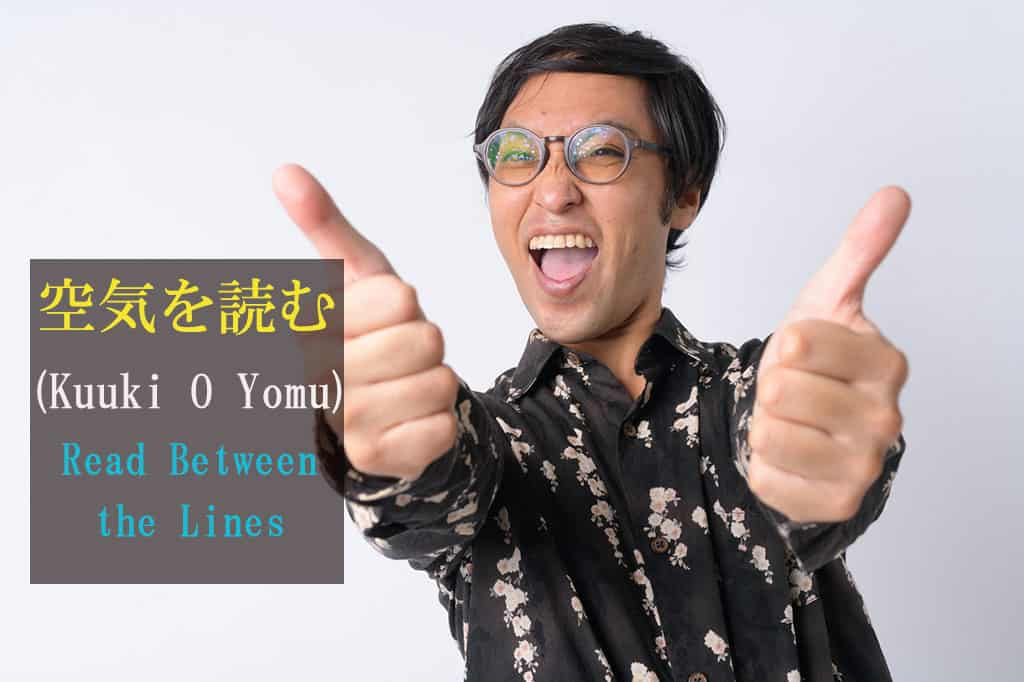 "A middle-aged Asian man with glasses giving two thumbs up. He has a huge smile. The Japanese and English text are for the word ""KY - Read-the-Air"" which is written on the left side of the image."