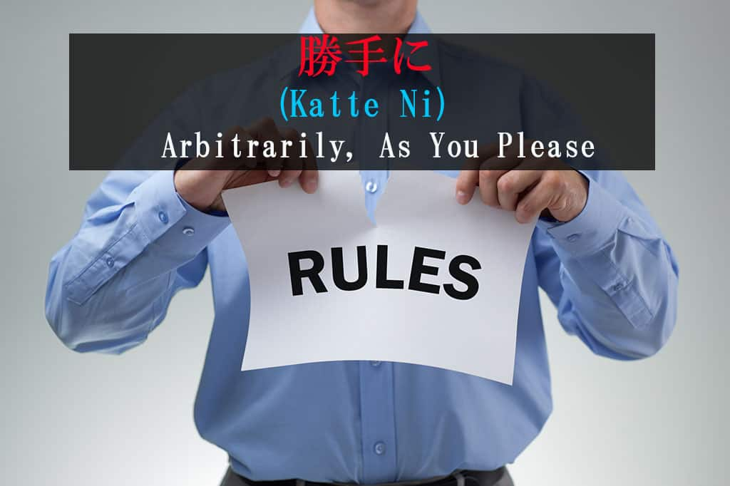 "A man wearing a blue, button down shirt holding a white sign with the word ""RULES"" written on it in black. He is tearing this paper with both hands. The Japanese and English for the word ""Katte-ni - As-You-Please"" is written at the top of the image."