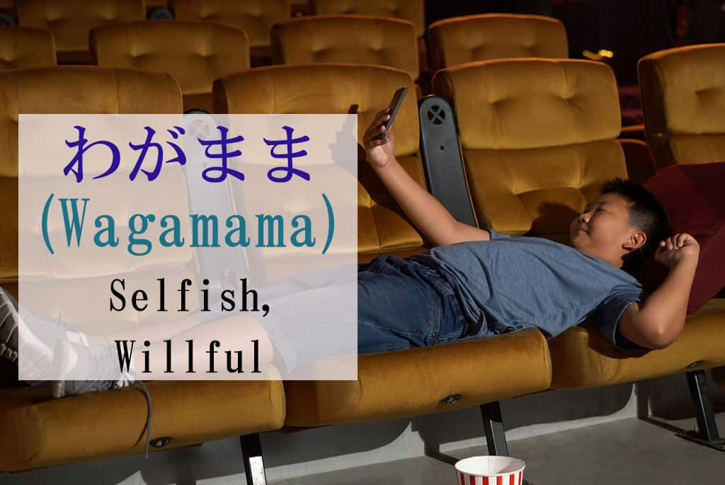 "A young, large, Asian boy using 4 chairs in what seems like a theater to lie down across the chairs. He is also using a pillow while looking at a smartphone. The Japanese and English displayed to the left are for the word ""Wagamama - Selfish."""