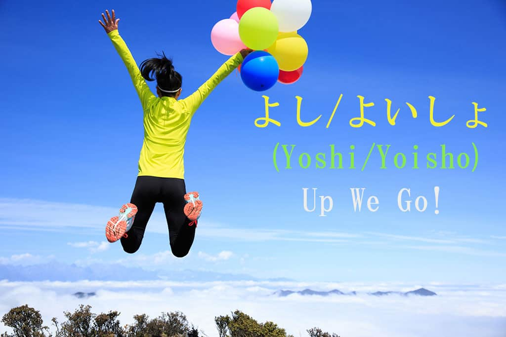 "A woman standing at a place of elevation looking over nature (trees and clouds) is holding a bunch of multicolored ballons in her right hand while she is jumping up. The Japanese and English written to the right are for the word ""Yooshi-Here-I-go."""