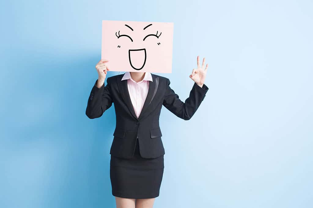 A woman in a business outfit with a pink board that has a happy face drawn on it, which she is holding in front of her face.