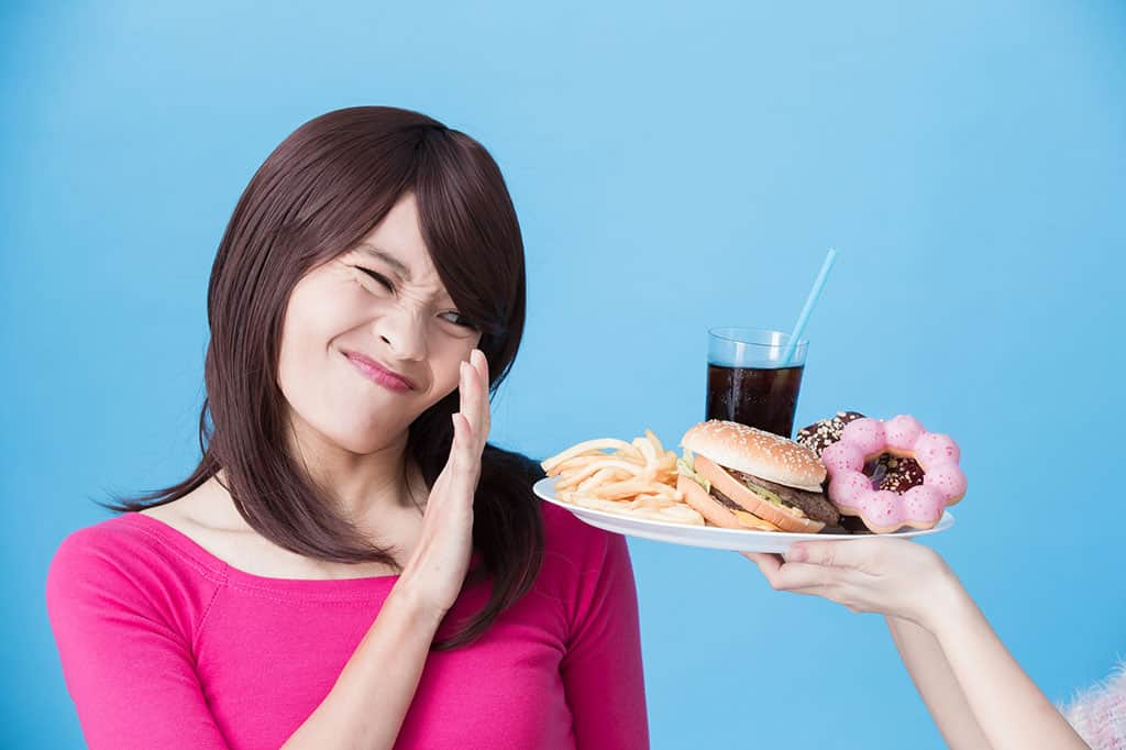 An Asian woman in a pink outfit putting out her hand to refuse a plate full of unhealthy food (french fries, hamburger, donuts, soda).
