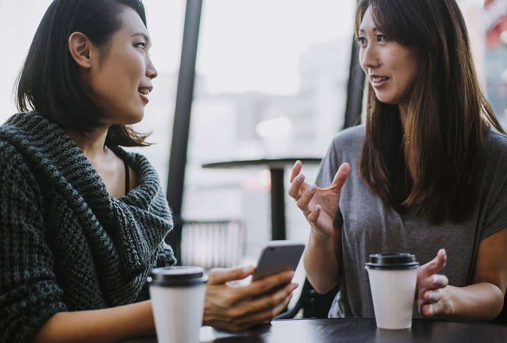 Two young Asian women sitting down at a table with their coffee having a conversation.