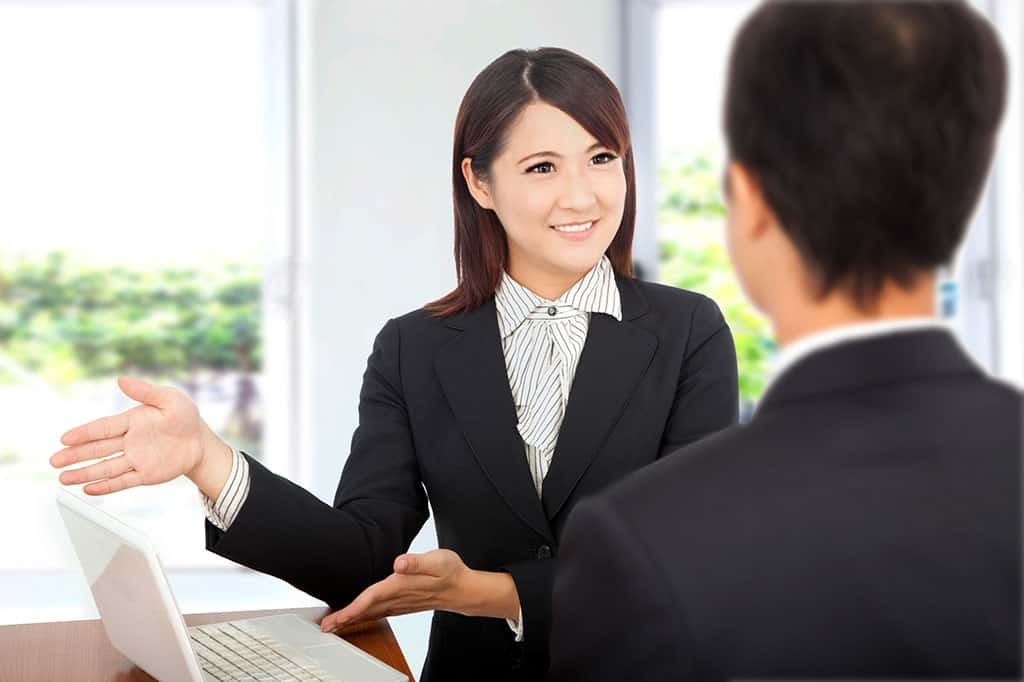 A young Asian woman in business attire using her hands to gesture to a laptop on the table. There is a man in front on her, which we can only see the back of his head.