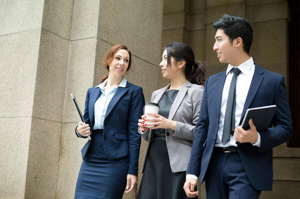A group of 3 young people in business attire, standing next to each other having a conversation.